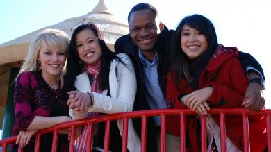 Four CCD students leaning on a red metal railing