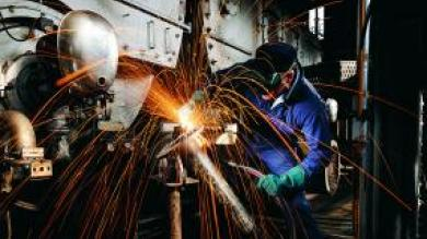 man in a machining helmet working with sparks