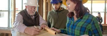 a male student and a female student look at blueprints with a man at a construction site
