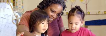 a woman works with two small children
