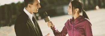 woman holds a microphone interviewing a man