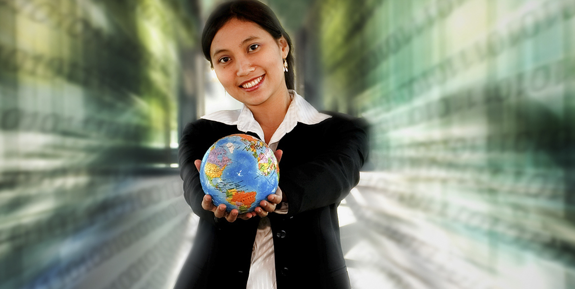 Woman wearing a suit holding a globe in outstretched hands