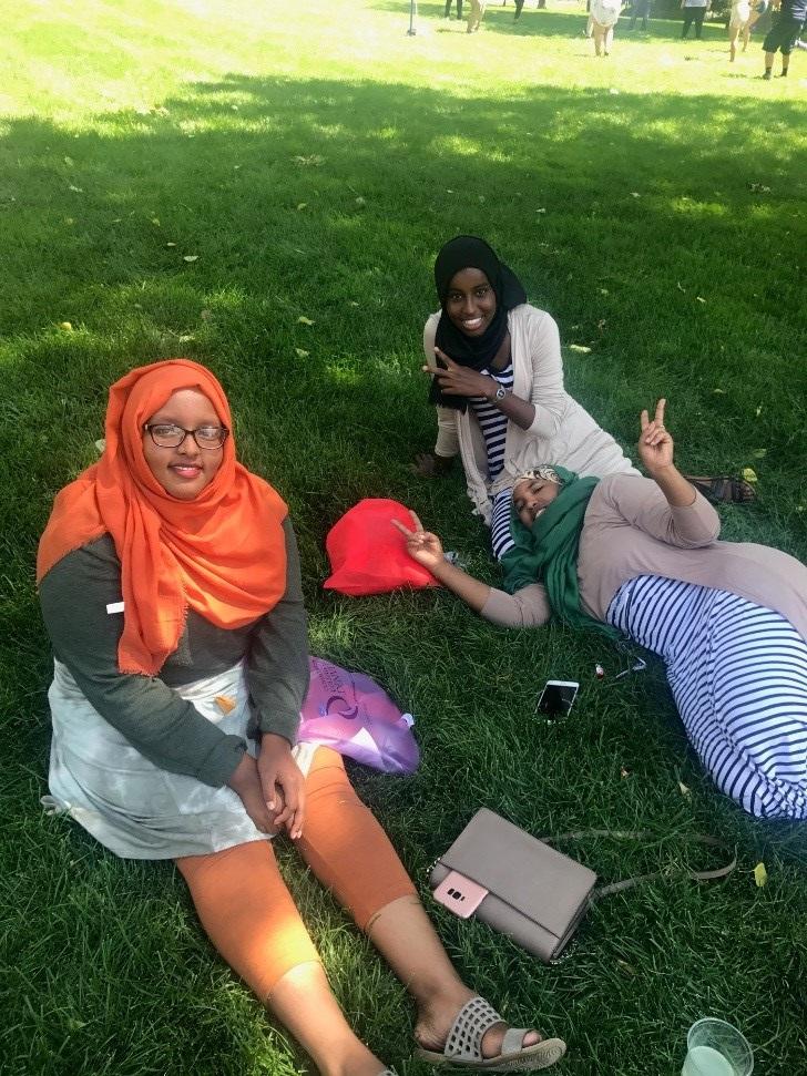 three famales sitting in grass