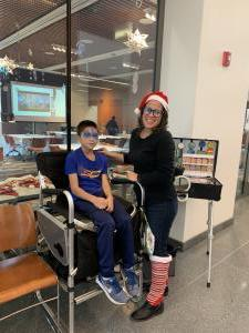 Boy in blue shirt and woman in Santa hat posing for a picture after getting face painted